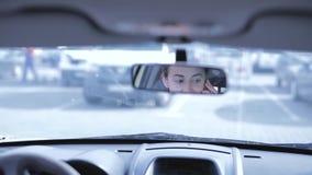 Mulher moreno que fala em um telefone celular ao conduzir um carro vista traseira através do espelho de rearview filme