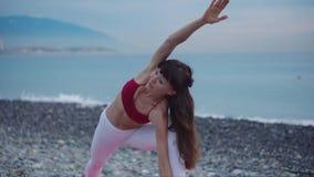Mulher moreno que faz a ioga exterior na praia filme