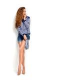 Mulher moreno que guarda falhanços de aleta do verão em listras azuis e em jea Imagem de Stock Royalty Free