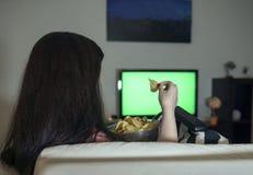 Mulher moreno que senta em casa a noite de relaxamento que come microplaquetas de batata e que olha a televisão, uma tela verde fotografia de stock royalty free