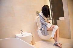 Mulher moreno que senta-se no toalete no banheiro fotografia de stock