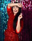Mulher moreno que tem o divertimento no partido menina de sorriso feliz em um vestido vermelho glamoroso à moda com sopros em um foto de stock royalty free