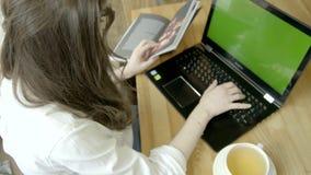 Mulher moreno que usa o PC do portátil com tela verde, chá bebendo no café Vista traseira Chave do croma vídeos de arquivo