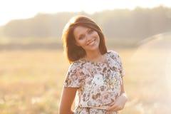 Mulher moreno 'sexy' bonita fora em um por do sol Foto de Stock Royalty Free