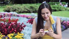 Mulher moreno 'sexy' bonita que espera no jogo do café da bebida do parque no chec do bom tempo do verão da flor do sorriso do te filme