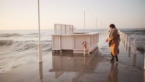 Mulher morno-vestida exterior do movimento lento que salta com o cão agradável na trela perto do beira-mar filme