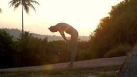 A mulher mostra asanas do namaskara do surya no movimento lento da trilha filme