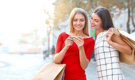 A mulher mostra em um telefone celular algo a sua amiga imagens de stock royalty free