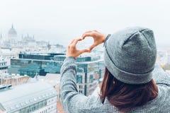 A mulher mostra o coração com mãos com vista bonita da cidade europeia velha no fundo Fotografia de Stock Royalty Free