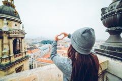 A mulher mostra o coração com mãos com vista bonita da cidade europeia velha no fundo Foto de Stock Royalty Free