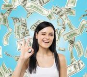 A mulher mostra o sinal aprovado As notas do dólar estão caindo para baixo sobre o fundo azul Fotografia de Stock Royalty Free