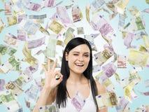 A mulher mostra o sinal aprovado As notas do Euro estão caindo para baixo sobre o fundo azul Fotografia de Stock