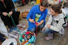 A mulher mostra que a menina uma classe mestra faz crochê sobre o tapete dos panos reciclados no dia da cidade em Moscou Fotos de Stock