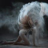 A mulher mostra um desempenho com farinha Imagem de Stock