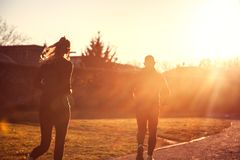 Mulher movimentando-se e homem desportivo que correm sobre a luz do sol de incandescência, Spor imagem de stock