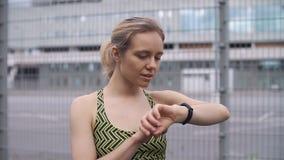 A mulher movimentando-se verifica seu dispositivo wearable vídeos de arquivo
