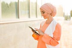 Mulher muçulmana árabe moderna com tablet pc fora Imagens de Stock