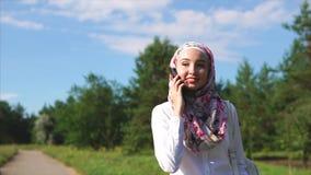 Mulher muçulmana alegre que fala ao amigo no móbil durante a caminhada filme