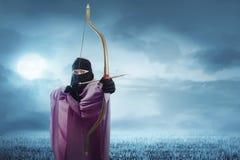 Mulher muçulmana asiática nova no hijab pronto para disparar em uma seta Fotografia de Stock