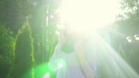 Mulher muçulmana atrativa à moda nova no hijab e vidros que falam no telefone, sunflare Mo lento vídeos de arquivo
