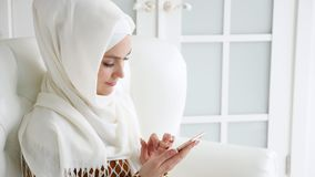 A mulher muçulmana atrativa no hijab está consultando páginas de Internet no smartphone que senta-se no sofá