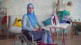 A mulher muçulmana bonita desabilitou em uma cadeira de rodas, fazendo os trabalhos de casa, passando a roupa vídeos de arquivo