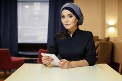 Mulher muçulmana bonita na roupa islâmica que senta-se em uma tabela com uma tabuleta eletrônica em suas mãos imagem de stock