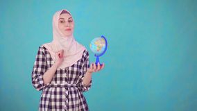 Mulher muçulmana bonita nova com o modelo do globo que olha o sorriso da câmera video estoque