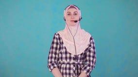 Mulher muçulmana bonita nova com os auriculares do telefone, olhando a câmera e o sorriso vídeos de arquivo