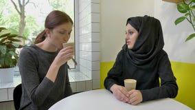 Mulher muçulmana bonita nova no hijab que diz algo à outra mulher, café bebendo, sentando-se no café video estoque