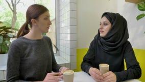 A mulher muçulmana bonita nova no hijab que diz algo à outra mulher, sentando-se no café, preocupou-se e ansioso filme