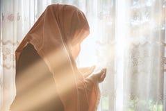Mulher muçulmana com rezar do hijab interno na janela brilhante Fotografia de Stock