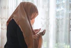 Mulher muçulmana com rezar do hijab interno na janela brilhante Foto de Stock