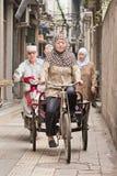 A mulher muçulmana dá um ciclo em uma aleia na área islâmica Xi no `, China Fotografia de Stock