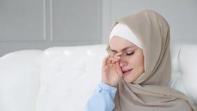 A mulher muçulmana de grito triste no hijab está sentando-se no sofá em casa