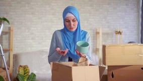 A mulher muçulmana desembala uma caixa dos pratos durante o movimento e encontra dano