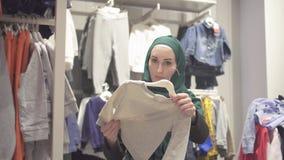 A mulher muçulmana em um hijab e em uma trouxa escolhe a roupa em uma loja das crianças em um shopping vídeos de arquivo