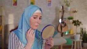 A mulher muçulmana em um hijab olha no espelho em sua cicatriz de uma queimadura em seus cara e gritos vídeos de arquivo