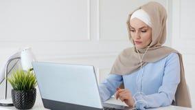 A mulher muçulmana está aprendendo o inglês nos fones de ouvido que usam em linha o computador vídeos de arquivo