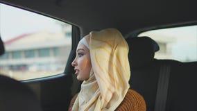 Mulher muçulmana feliz em um carro em um assento traseiro do passageiro filme