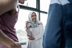 Mulher muçulmana feliz na conversação com amigo imagens de stock royalty free