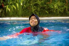 Mulher muçulmana feliz nova que joga com água excitada na piscina do recurso que espirra e que tem o divertimento que veste o Isl fotos de stock