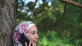 Mulher muçulmana feliz que fala em exterior móvel vídeos de arquivo