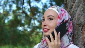 Mulher muçulmana feliz que fala em exterior móvel filme