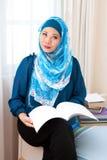 Mulher muçulmana malaio que aprecia uma leitura de relaxamento do tempo foto de stock