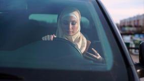 Mulher muçulmana moderna Senta-se em um assento do ` s do motorista e usa-se o smartphone vídeos de arquivo