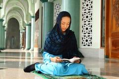 Mulher muçulmana na leitura Qur'an da mesquita imagem de stock royalty free