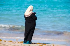 Mulher muçulmana na veste preta e no lenço principal branco que olham seu c fotografia de stock royalty free