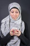 Mulher muçulmana no hijab que guarda um telefone celular Imagens de Stock