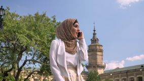 Mulher muçulmana nova atrativa no hijab que anda no parque e que fala no telefone, baixo ângulo, dia ensolarado exterior vídeos de arquivo